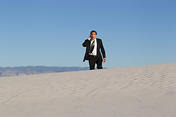 businessman on a cellphone while walking in a deserted desert in New Mexico