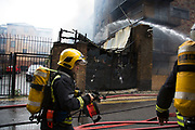 London, UK. Wednesday, May 18th 2016. Fire fighters tackle a fire in a block of flats in Brodlove Lane in Wapping, London, United Kingdom.