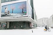 Brussel 12 maart 2013. Zware sneeuwbuien teisteren geheel Belgie. De langste files sinds tijden. Het verkeer, bussen, treinen hebben veel last van de sneeuw.In het centrum van de stad Brussel (Nieuwstraat) hangen  vrolijk gekleurde reclameborden met bloesem en fietsplezier. Op straat was iets minder zonnig. De lente is ver te zoeken.
