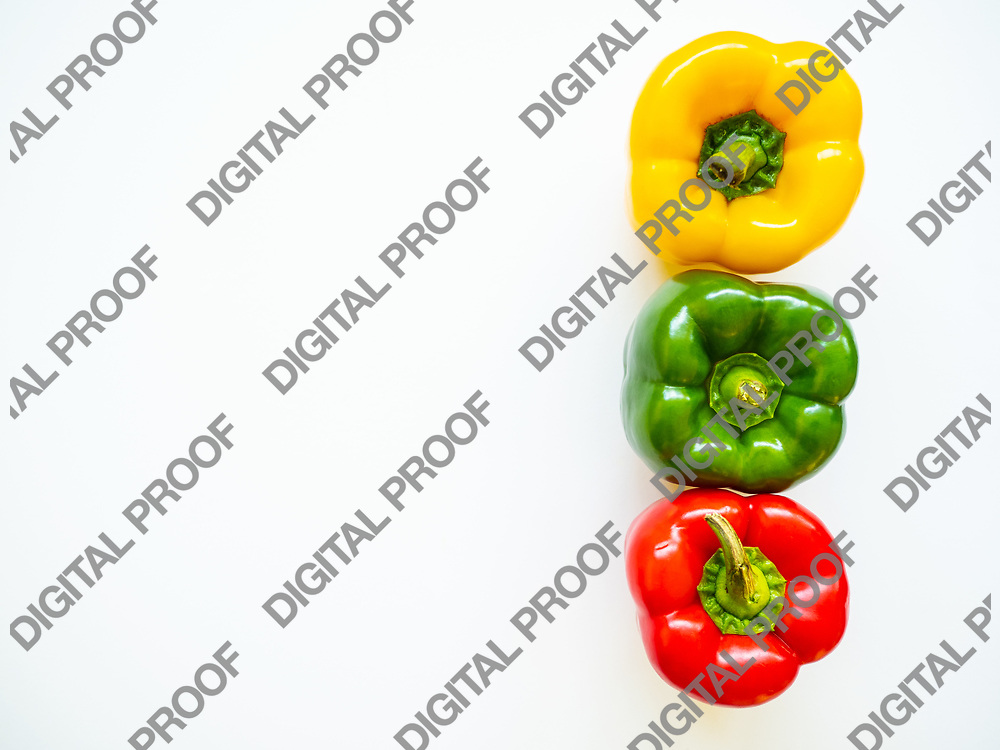 Red, green and yellow bell peppers isolated in white background viewed from above - flatlay look