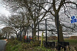 HS2 security contractors guard a fenced area on Leather Lane where several hundred-year-old oak trees have been felled to enable the construction of a temporary access road and compound for the HS2 high-speed rail link on 9th April 2021 in Great Missenden, United Kingdom. Following pressure from local residents, Buckinghamshire Council and the Chilterns Conservation Board, it appears that HS2 contractors have altered their plans in such a way as to preserve some of the trees lining the wildlife-rich ancient country lane.
