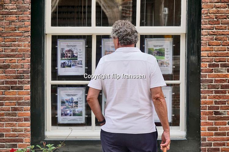 Nederland, Naarden, 24-7-2020  Een man bekijkt de advertenties voor huizen die te koop staan. Verschillenden zijn al snel verkocht. Er zitten huizen bij van meer als i miljoen euro, het duurdere segment .Foto: ANP/ Hollandse Hoogte/ Flip Franssen