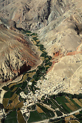 A village located along the Hindu Kush, the mountain range crossing Afghanistan and separating Kabul from Bamiyan, is photographed from a UNAMA helicopter on its way to the capital. The Buddhas of Bamiyan were two 6th century monumental statues of standing Buddhas carved into the side of a cliff in the Bamiyan valley in the Hazarajat region of central Afghanistan, situated 230 km northwest of Kabul at an altitude of 2500 meters. The statues represented the classic blended style of Gandhara art. The main bodies were hewn directly from the sandstone cliffs, but details were modelled in mud mixed with straw, coated with stucco. Amid widespread international condemnation, the smaller statues (55 and 39 meters respectively) were intentionally dynamited and destroyed in 2001 by the Taliban because they believed them to be un-Islamic idols. Once a stopping point along the Silk Road between China and the Middle East, researchers think Bamiyan was the site of monasteries housing as many as 5,000 monks during its peak as a Buddhist centre in the 6th and 7th centuries. It is now a UNESCO Heritage Site since 2003. Archaeologists from various countries across the world have been engaged in preservation, general maintenance around the site and renovation. Professor Tarzi, a notable An Afghan-born archaeologist from France, and a teacher in Strasbourg University, has been searching for a legendary 300m Sleeping Buddha statue in various sites between the original standing ones, as documented in the old account of a renowned Chinese scholar, Xuanzang, visiting the area in the 7th century. Professor Tarzi worked on projects to restore the other Bamiyan Buddhas in the late 1970s and has spent most of his career researching the existence of the missing giant Buddha in the valley.