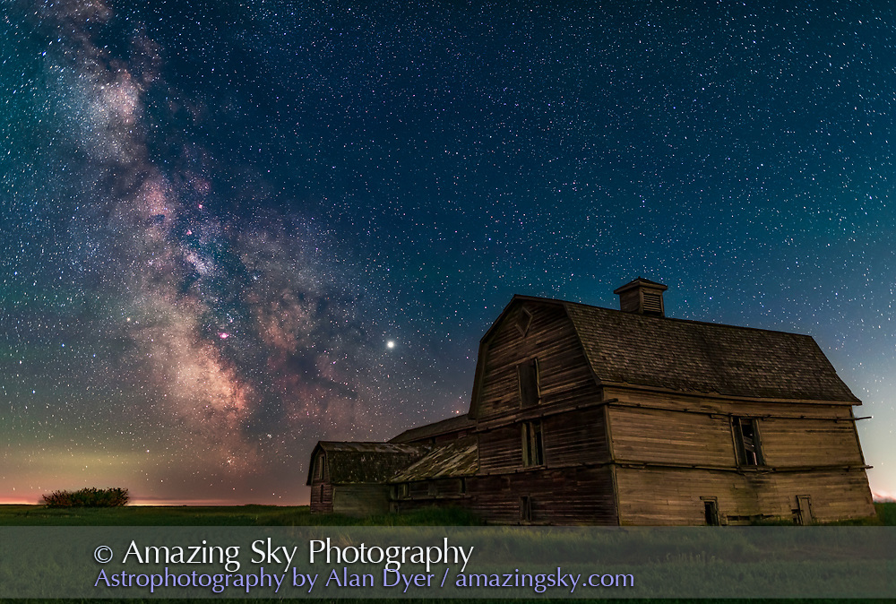 """The galactic centre area of the Milky Way in Sagittarius behind the grand old barn near home in southern Alberta, on June 30, 2019. Illumination of the barn is from twilight to the north, but also from light pollution skyglow from the west off frame at right.  The sky is blue from the perpetual summer twilight at this time of year. <br /> <br /> Jupiter is at centre. The nebulas and starclouds of the Milky Way show up well here. The southerly Messier clusters, M6 and M7, in Scorpius just skim the horizon at left. The very red star in the """"eye"""" of the Dark Horse is TW Ophiuchi. This is from my latitude of 51° N. <br /> <br /> This is a blend of tracked (for the sky) and untracked (for the ground) exposures, with a stack of 3 for the ground and 5 for the sky, stacked to smooth noise. All at ISO 1250 and one minute each, but with the sky exposures at f/2 and ground exposures at f/2.5, with the Sigma 24mm Art lens and stock (not modified) Nikon D750.  The sky exposures were through a NiSI Natural Night light pollution filter. The sky exposures are at f/2 to make up for the light loss from shooting thru the filter while keeping exposures short for ease of blending later. The tracker was the Sky-Watcher Star Adventurer.<br /> <br /> I added a mild Orton effect glow layer to the image using Luminar Flex."""