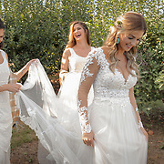 A bride and her sisters share a laugh as they help her walk to her wedding ceremony at Carrigan Farms in Mooresville.    ©Travis Bell Photography