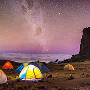 The brilliantly clear night sky at Lava Tower Camp (15,215 feet), with Lava Tower at right, clouds in the distance, and the Milky Way. Mt Kilimanjaro's Lemosho Route. Far beyond the tents you can see lights from a town far below. The band of light running near vertically through the sky is the Milky Way.
