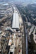 Nederland, Barendrecht, Stationsgebied, 08-03-2002; spoorlijn Rotterdam-Dordrecht, in Zuidelijke richting; om geluidsoverlast tegen te gaan ivm Betuweroute en HSL wordt een 1500 m lange overkapping gebouwd, met daarin opgenomen het nieuwe station (de langwerpige betonnen doos); de overkapping wordt nog aanmerkelijk verbreed tot en met de sporen van de haven spoorlijn (rechts met blauwgrijs tijdelijk perron), op deze plaats komt tzt de HSL te lopen; zie ook close up.bouwen verkeer en vervoer infrastructuur Betuwelijn.<br /> luchtfoto (toeslag), aerial photo (additional fee)<br /> foto /photo Siebe Swart