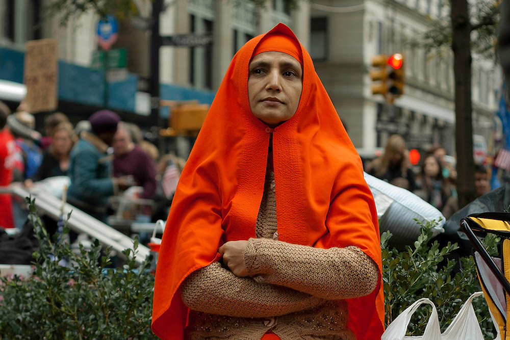Woman sitting as passersby take pictures during the Occupy Wall Street demonstration in Zuccotti Park. October 21, 2011