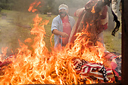12 SEPTEMBER 2020 - DES MOINES, IOWA: DAVID HOTT throws US flags into the fire during a flag retirement ceremony at Glendale Cemetery in Des Moines. About 10 volunteers came to the cemetery Saturday morning to properly dispose of about 4,000 American flags. The flags had flown over veterans' graves, local businesses, and state offices. The US Flag Code calls for used American flags to be respectfully disposed of in a fire.   PHOTO BY JACK KURTZ
