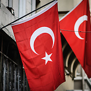 Two Turkish flags are displayed outside a building in Istanbul, Turkey. The Flag of Turkey is known in Turkish as Ay Yıldız (moon star) or Albayrak (Red flag).