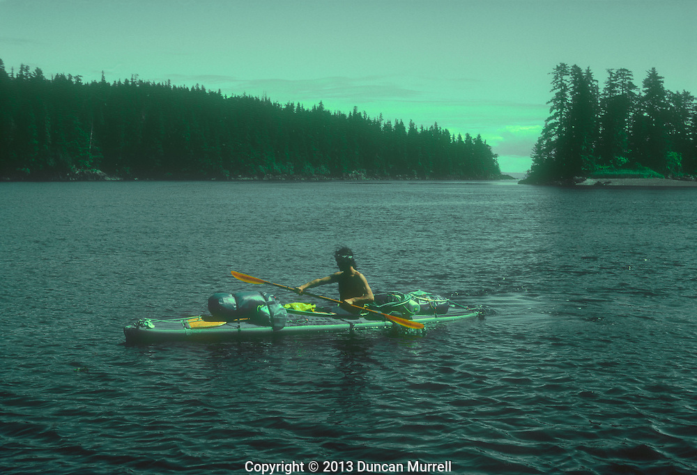 Duncan Murrell paddling his fully laden Klepper Aerius 1 folding kayak, the Brothers Islands, Stephen's Passage, Southeast Alaska, USA.<br /> <br /> It was always a relief to get everything packed into and onto my kayak. I broke all of the conventional rules regarding how much could be loaded onto the decks, but I was carrying such a heavy load with all of my camping and photographic equipment as well that my kayak was still very stable, if not a little heavy to paddle, but after paddling so many miles like that and keeping up with the whales day after day I developed a strong paddling style all of my own.