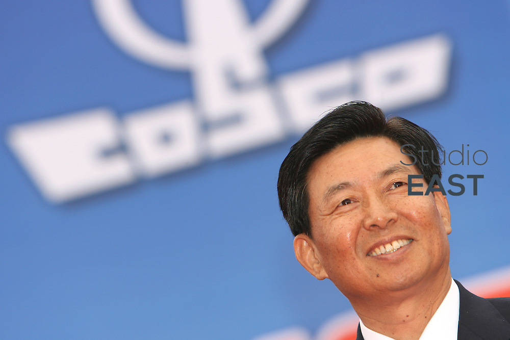 NINGBO, CHINA - March 22: Wei Jiafu, Chairman of COSCO (China Ocean Shipping Co.) Group, smiles under his company's logo during a ship launch ceremony on March 22, 2006 in Ningbo, China. Shares in Cosco Holdings nearly doubled on their first day of trading in Shanghai on June 26, 2007 after China's largest shipping group received record subscriptions for its $2bn offering. (Photo by Servais Mont/Getty Images)