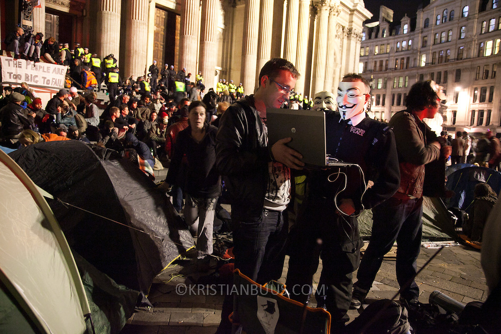 One of the Anonymous speaks to streamed activist media. The London Stock Exchange was attempted occypied in solidarity with Occupy Wall in Street in New York and in protest againts the economic climate, blamed by many on the banks. Police managed to keep people away fro the Patornoster Sqaure and the Stcok Exchange and thousands of protestors stayid in St. Paul's Square, outside St Paul's Cathedral. Many camped getting ready to spend the night in the square.