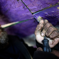 David Drap, 43, who identifies himself as homeless and a heroin user, removes a screw from a plyboard wall dividing the Rt. 95 overpass and a newly built set of apartments in order to build his own shelter.   Drap, who lives there with his wife and tabby cat, spoke with Sam Santiago, a Project H.O.M.E. outreach response worker.  This Philadelphia organization that helps the homeless is having a $300 million fundraising effort.