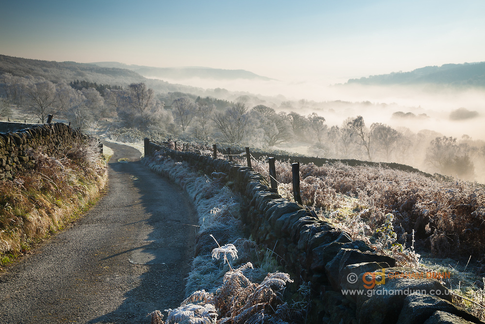 Bright morning light, heavy frost and a stunning temperature inversion in the Derwent Valley. Captured near to Greenwood Farm, below Millstone Edge. A winter sunrise in the Derbyshire Peak District.