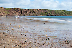 As the calm blue sea of Filey Bay recedes people walk the beach from Coble Landing at Filey towards Filey Brigg