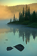 Northern lake in fog at sunrise<br />