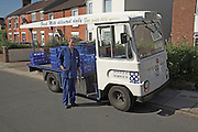 Milkman and electric powered vehicle delivering milk  from house to house, Ipswich, Suffolk, England