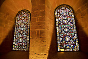 Lay Brothers Dormitory and stained glass windows at Fontfroide Abbey near Narbonne, France. Fontfroide Abbey is a former Cistercian monastery in France, situated 15 kilometers south-west of Narbonne. It was founded in 1093 by Aimery I, Viscount of Narbonne, but remained poor and obscure, and needed to be refounded by Ermengarde, Viscountess of Narbonne. The abbey fought together with Pope Innocent III against the heretical doctrine of the Cathars who lived in the region. It was dissolved in 1791 in the course of the French Revolution. The premises, which are of very great architectural interest, passed into private hands in 1908, when the artists Gustave and Madeleine Fayet dAndoque bought it to protect the fabric of the buildings from an American collector of sculpture. They restored it over a number of years and used it as a centre for artistic projects. It still remains in private hands. Today it is open to paying guests.
