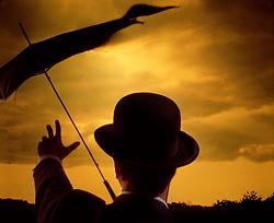 man gentlman in bowler hat reaches toward umbrella copy space CONCEPT STOCK PHOTOS CONCEPT STOCK PHOTOS