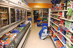 Shop assistant with learning disability tidying and stocking shelves in supermarket,
