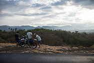 Bali, Indonesia - September 24, 2017: Four Indonesian youth and two motorbikes on the side of a road above Banjar, Bali, Indonesia.