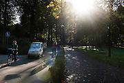 Fietsers en een brommobiel in het Wilheminapark in Utrecht bij een mooie herfstzon.<br /> <br /> Traffic at the WIlhelminapark in Utrecht in autumn.