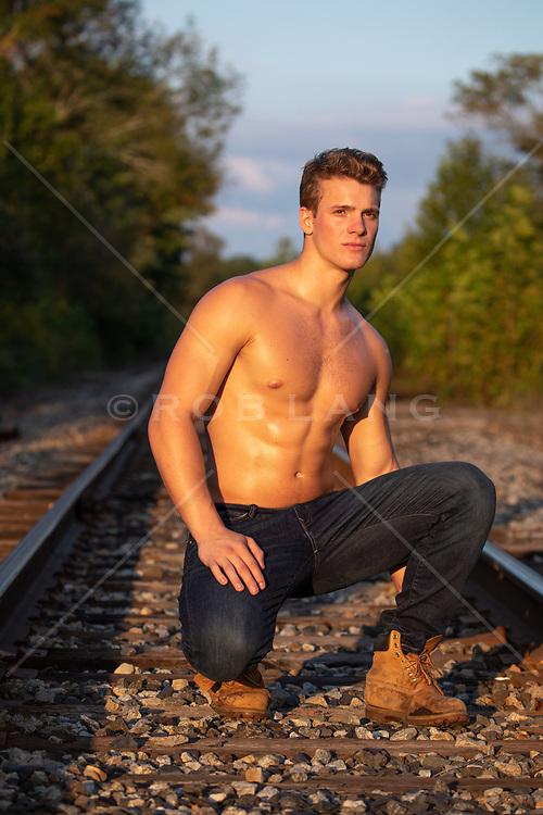 shirtless muscular man on railroad tracks at sunset