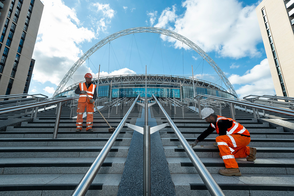 © Licensed to London News Pictures. 15/04/2021. LONDON, UK.  Construction workers on the soon to be completed Olympic Steps at Wembley Stadium.  The 48 Olympic Steps comprises 4 flights of 12 steps and will become the new gateway to the stadium for visitors and fans arriving from Olympic Way and is due to be completed in June 2021 in time for England group stage matches at Euro 2020.  Photo credit: Stephen Chung/LNP