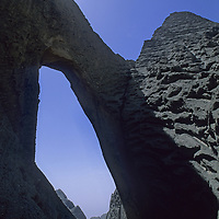 A tiny climber stands atop massive Shipton's Arch in the Kara Tagh Mountains near Kashgar and the Taklimakan Desert.