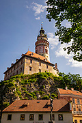 The castle tower is a landmark of Cesky Krumlov and a symbol of its artistic beauty. It was built in the 13th century and rebuilt in the Renaissance style around 1580. Crucifixion stature is in the foreground