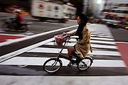 Een vrouw fietst op een vouwfiets door Tokyo, wat gezien de drukte niet zonder gevaar is.