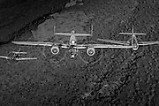 B-25 Mitchell P-51 Mustang and TBM Avenger flying in formation over Arizona desert in monochrome image