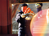 South Korea, Busan, 2001. Winter persimmons are offered to Buddha at Busan's Pomosa Temple, far up in the forested hillsides behind the city.