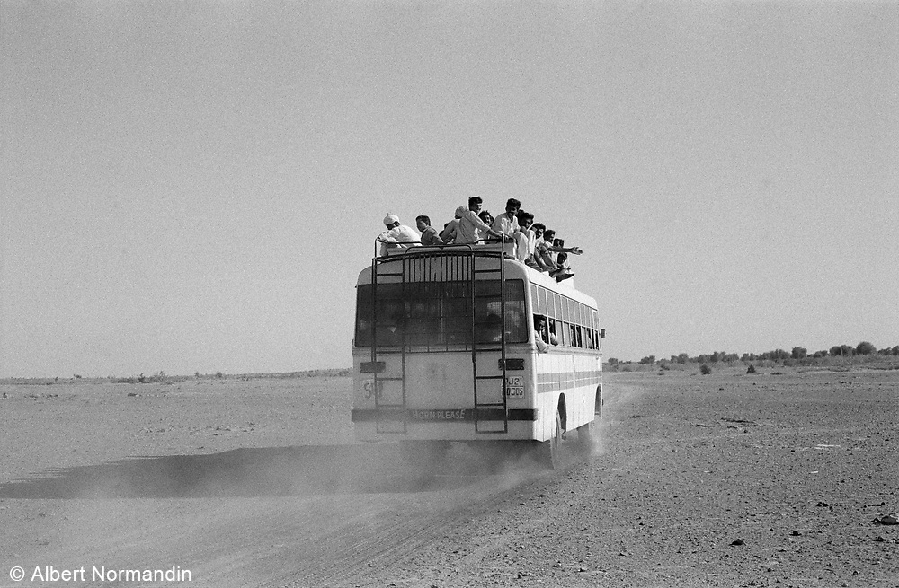 Over crowded bus leaving village in dust, waving