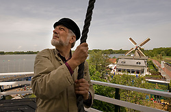 """Jaap Bes is the head volunteer miller at the De Ster snuff and spice mill in Rotterdam. Bes stands on the """"stage,"""" a platform midway up the windmill's structure, and pulls the mill brake to stop the mills' wings from turning. (Client: Wired.com / Photo © Jock Fistick)"""