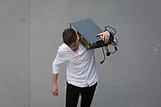A man carries electronic equipment on his shoulder in the City of London - the capitals financial district, on 21st August 2018, in London, England.