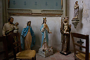 Plaster Catholic idols in a corner of the Saint-Gervais-Saint-Protais church at Le Grand-Pressigny, Indre-et-Loire, France. The Virgin Mary is seen iin blue and a small child is held in the arms of a monk on the right. <br /> The Gothic style church has its origins in the 12th century but has been added to and amended over the centuries like so many other ancient places of worship here in the Loire Valley and the rest of the country.
