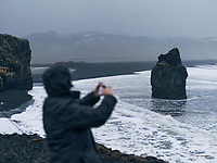 Tourist photographing at Dyrhólaey Peninsula in winter, South Iceland.