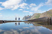 A couple is walking on the seashore at Senja, Norway. The montains in the background is unformal called The Devils Jaw | Et par som spaserer i strandkanten på Tungeneset, Senja. I bakgrunnen ser vi fjella som populært kalles Djevelens Tanngard.