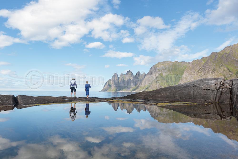A couple is walking on the seashore at Senja, Norway. The montains in the background is unformal called The Devils Jaw   Et par som spaserer i strandkanten på Tungeneset, Senja. I bakgrunnen ser vi fjella som populært kalles Djevelens Tanngard.