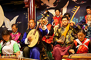 Elderly and young musicians in a Naxi Orchestra, a Naxi minority group playing at the Naxi Music Academy, Naxi Guyue Hui, in Old Town Lijiang, Yunnan province, China. The beautiful repetitive music they produce has been lost elsewhere in China and is threatened even here in Lijiang due to it's ageing players. The instruments played did not survive the Cultural Revolution in most parts of China, but several members of the Naxi group hid theirs by burying them, to revive them in 1978 after the revolution. Music from the Han, Tang, Song and Yuan Dynasties is played.