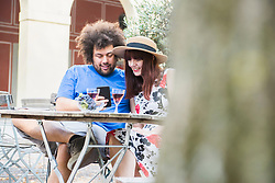 Young couple using mobile phone at outdoor restaurant