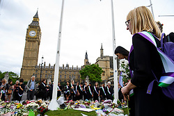 © Licensed to London News Pictures. 22/06/2016. London, UK. Flowers being placed outside the Houses of Parliament by members of NGO's, ahead of a memorial service to mark the life of the Labour MP for Batley and Spen, Jo Cox, who was murdered near her constituency office.  Jo Cox would have turned 42 today. Photo credit: Ben Cawthra/LNP