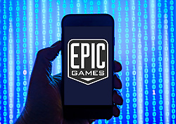 Person holding smart phone with Epic Games logo displayed on the screen. EDITORIAL USE ONLY
