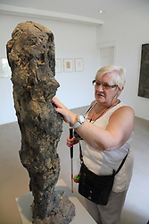 Woman with visual impairment touching a sculpture at Yorkshire Sculpture Park.