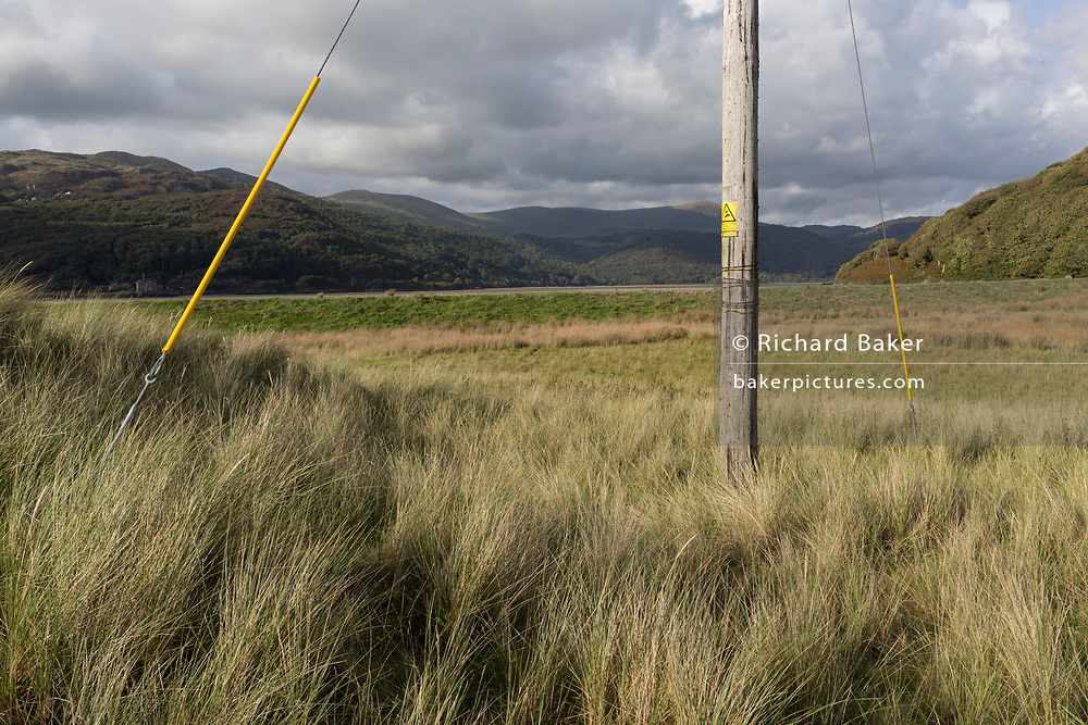 A landscape of coastal grasses, distant hills and a Welsh Power electricity power pole, on 13th September 2018, in Barmouth, Gwynedd, Wales.