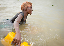 © Licensed to London News Pictures. 05/07/2013. Koulikoro,  Mali.  Balas (13) sweeps the water dredging for sand.  She will spend 8 hours a day dredging the water for the sand which has been dropped by other workers.  The sand is transported to the shore which is then delivered across Mali for use within the construction industry.   Photo credit: Alison Baskerville/LNP