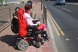 Wheelchair user with cerebral palsy waiting at pedestrian crossing.