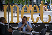 """With the word 'Meet"""" in the background, two businessmen chat at a table outside a City bar, in the City of London, the capital's financial district, on 22nd June 2021, in London, England."""